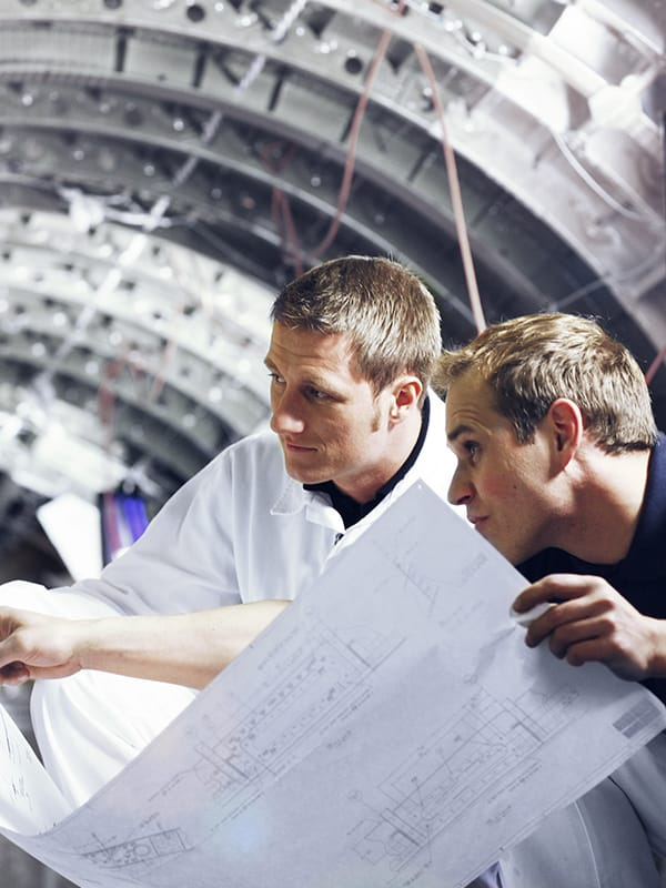 Two engineers discussing plans inside an aircraft fuselage.