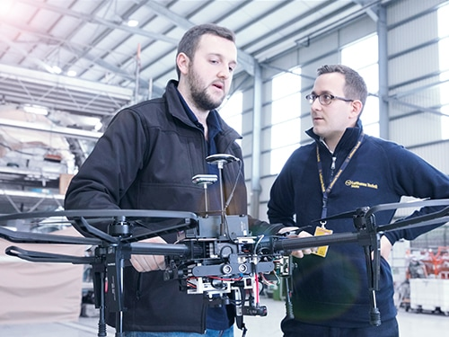 Innovation bay: Two engineers discussing the use of a drone in base maintenance.