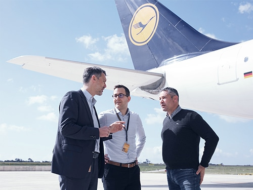Three Man standing on the airdrome infront of a Lufthansa plane.